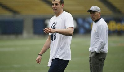 In this March 24, 2017, photo, California quarterback Davis Webb, left, smiles as Jim Zorn, right, watches during NFL football pro day in Berkeley, Calif. The key task for Webb leading up to this month's NFL draft is to prove to teams that he is more than a product of the Air Raid offense and has the traits that will translate to being a professional. Webb heads into the draft with a bit of a stigma after spending three years running that spread offense at Texas Tech and then California as a graduate transfer. (AP Photo/Eric Risberg)