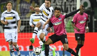 Hertha's Sami Allagui and Moenchengladbach's Andreas Christensen, from right, challenge for the ball during the German Bundesliga soccer match between Borussia Moenchengladbach and Hertha BSC Berlin in Moenchengladbach, Germany, Wednesday, April 5, 2017. (AP Photo/Martin Meissner)