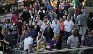 In this April 4, 2017, photo, people walk along the Las Vegas Strip in Las Vegas. More than 42 million people visited Las Vegas in 2016, according to a report from the resort's biggest travel booster released Wednesday, April 5. (AP Photo/John Locher)