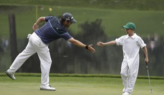 Louis Oosthuizen of South Africa, high fives Jacob Immelman on the ninth hole during the par three competition at the Masters golf tournament Wednesday, April 5, 2017, in Augusta, Ga. (AP Photo/David Goldman)
