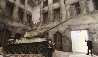 FILE- In this Monday, Jan. 23, 2017 file photo, a woman stands in front of an exhibit in the Museum of the Second World War in Gdansk, Poland. A court has opened the way for Poland's populist government to take control of a new World War II museum that has been the focus of a major ideological battle over how to remember the war. (AP Photo/Czarek Sokolowski, File)