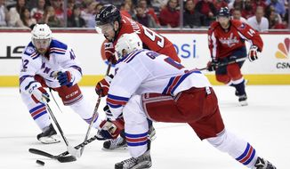 Washington Capitals center Evgeny Kuznetsov (92), of Russia, skates with the puck against New York Rangers defensemen Dan Girardi (5) and Brendan Smith (42) during the second period of an NHL hockey game, Wednesday, April 5, 2017, in Washington. (AP Photo/Nick Wass)