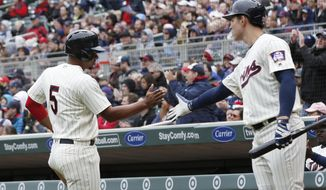 Minnesota Twins' Eduardo Escobar, left, is greeted by Max Kepler after scoring on a sacrifice ground out in the second inning of a baseball game Wednesday, April 5, 2017, in Minneapolis.  (AP Photo/Jim Mone)