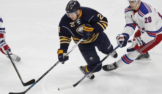 FILE - In this Dec. 1, 2016, file photo, Buffalo Sabres forward Kyle Okposo (21) is tripped up New York Rangers forward Derek Stepan (20) during an NHL hockey game in Buffalo, N.Y. Okposo has spent the past three days in a Buffalo hospital undergoing a battery of tests to determine an undisclosed illness that has sidelined him for more than a week. A person with direct knowledge of Okposo's status confirmed to The Associated Press on Wednesday, April 5, that the player is in the neuro surgical intensive care unit at Buffalo General Hospital. The person spoke on the condition of anonymity because the Sabres have not revealed Okposo has been hospitalized. (AP Photo/Jeffrey T. Barnes, File)
