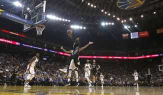 Minnesota Timberwolves forward Shabazz Muhammad (15) drives to the basket against Golden State Warriors forward Matt Barnes during the first half of an NBA basketball game Tuesday, April 4, 2017, in Oakland, Calif. (AP Photo/Tony Avelar)
