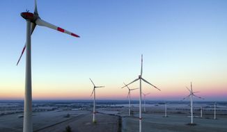 The sun is rising in the morning sky above a landscape with a wind energy park near Jacobsdorf, Germany, in this Dec. 31, 2016, file photo. U.N.-backed report says global investments in renewable energy fell by almost a quarter last year amid a drop in prices and lower spending in some markets. The United Nations Environment Program said Thursday, April 6, 2017, that overall investments reached $241.6 billion last year, down from $312.2 billion in 2015.  (Patrick Pleul/dpa via AP,file)