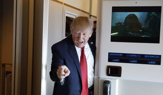 President Donald Trump points to a reporter as he arrives to meet with reporters on Air Force One while in flight from Andrews Air Force Base, Md., to Palm Beach International Airport, Fla., Thursday, April 6, 2017. (AP Photo/Alex Brandon)