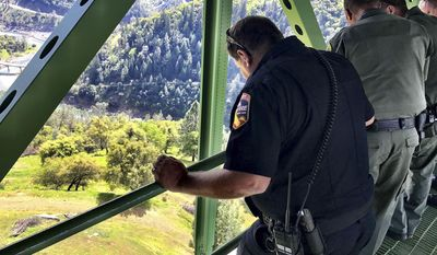 In this photo provided by the Placer County Sheriff's Office, sheriff's and other officials look where a woman fell 60 feet while trying to take a selfie on the 730-foot-tall Foresthill Bridge, Wednesday, April 5, 2017, near Auburn, Calif. The sheriff's office says the woman was airlifted to Sutter Roseville Medical Center and is expected to survive. (Placer County Sheriff's Office via AP)