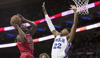 Chicago Bulls' Jimmy Butler, left, goes up for the shot with Philadelphia 76ers' Richaun Holmes, right, defending the basket during the first half of an NBA basketball game, Thursday, April 6, 2017, in Philadelphia. (AP Photo/Chris Szagola)