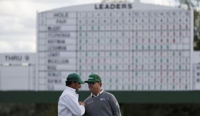 Charley Hoffman shakes hands with his caddie Brett Waldman after finishing the first round of the Masters golf tournament Thursday, April 6, 2017, in Augusta, Ga. (AP Photo/David Goldman)