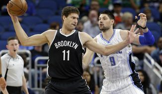 Brooklyn Nets' Brook Lopez (11) looks for a way to the basket around Orlando Magic's Nikola Vucevic (9) during the first half of an NBA basketball game, Thursday, April 6, 2017, in Orlando, Fla. (AP Photo/John Raoux)