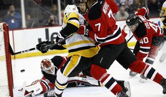 Pittsburgh Penguins right wing Bryan Rust, center, scores a goal as New Jersey Devils goalie Cory Schneider, bottom, defenseman Jon Merrill (7) and center Blake Coleman (40) defend during the first period of an NHL hockey game, Thursday, April 6, 2017, in Newark, N.J. (AP Photo/Julio Cortez)