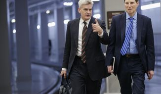 Sen. Bill Cassidy, R-La., left, walks with Sen. Ron Wyden, D-Ore., as they arrive for the scheduled cloture vote to end debate on President Donald Trump's Supreme Court nominee Neil Gorsuch, on Capitol Hill in Washington, Thursday, April 6, 2017. (AP Photo/J. Scott Applewhite)