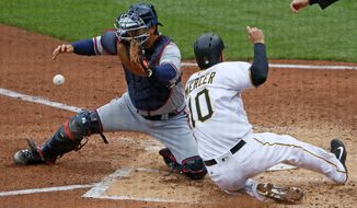Pittsburgh Pirates' Jordy Mercer (10) scores on a double by Starling Marte off Atlanta Braves starting pitcher Mike Foltynewicz, as Braves catcher Kurt Suzuki receives the late relay throw during the fourth inning of a baseball game in Pittsburgh, Friday, April 7, 2017. (AP Photo/Gene J. Puskar)