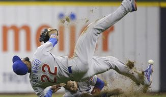 Chicago Cubs' Jason Heyward (22) and Javier Baez collide while trying to catch a double off the bat of Milwaukee Brewers' Hernan Perez during the sixth inning of a baseball game Friday, April 7, 2017, in Milwaukee. Baez left the game after the collision. (AP Photo/Jeffrey Phelps)