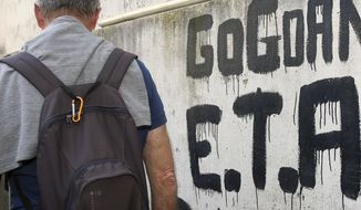 """A man walks past graffiti reading """"ETA , Basque country and Freedom"""", in Sare, southwestern France, Friday, April 7, 2017. The armed Basque separatist group ETA, inactive for more than five years, is to hand over its arms Saturday, a finishing touch to a 43-year violent campaign that claimed 829 lives, mostly in Spain. (AP Photo/Bob Edme)"""