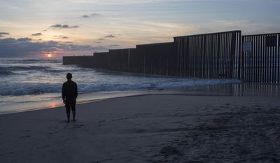 In this Tuesday, April 4, 2017 photo, man who gave his name as Hugo stands on the shore of the Pacific Ocean as his friend films him, backdropped by the US-Mexico border fence that separates Tijuana, Mexico, from San Diego, Calif. (AP Photo/Rodrigo Abd)