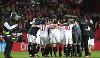 "FILE - In this Jan. 15, 2017 file photo, a TV camera operator films Sevilla players celebrating at the end of the match during La Liga soccer match against Real Madrid at the Ramon Sanchez Pizjuan stadium, in Seville, Spain. La Liga is sending a clear message that it will not allow piracy to get in the way of its fight with the Premier League as it needs every possible source of income to try to compete financially with the powerful English league. It resorts to a proprietary tool to monitor the internet and uses a group of ""online guards"" to denounce illegal broadcasts of games. (AP Photo/Angel Fernandez, File)"