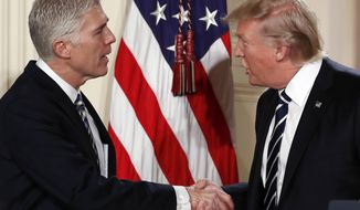 FILE - In this Jan. 31, 2017, file photo, President Donald Trump shakes hands with Judge Neil Gorsuch in East Room of the White House in Washington, as he announces Grouch as his nominee for the Supreme Court. With Gorsuch on the verge of confirmation to the Supreme Court, Trump is nearing his first major legislative achievement. It will be victory for the insiders. (AP Photo/Carolyn Kaster, File)