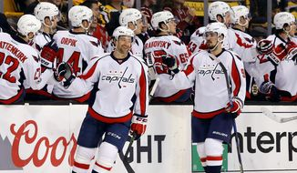 Washington Capitals' Justin Williams, left, and Dmitry Orlov (9) are congratulated at the bench after Williams scored against the Boston Bruins during the second period of an NHL hockey game in Boston, Saturday, April 8, 2017. (AP Photo/Winslow Townson)