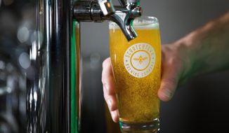 Shay Reilly pours a Big Joe pilsner at Scratchtown Brewing Company Thursday, March 16 2017, in Ord, Neb.  In a town of 2,100 people, three business partners, an electrician, an ex-banker and a former Omaha Chamber of Commerce executive, are brewing what may be the best craft beer in the entire state.  (Rebecca Gratz/Omaha World-Herald via AP)