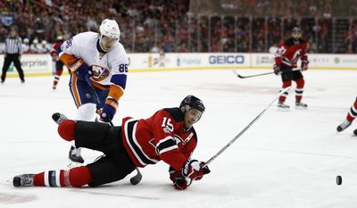 New Jersey Devils center Travis Zajac (19) hits the ice while being challenged by New York Islanders left wing Nikolay Kulemin (86), of Russia, during the second period of an NHL hockey game, Saturday, April 8, 2017, in Newark, N.J. (AP Photo/Julio Cortez)