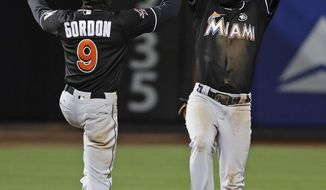 Miami Marlins' Dee Gordon, left, and Adeiny Hechavarria celebrate after the team's baseball game against the New York Mets on Friday, April 7, 2017, in New York. The Marlins won 7-2. (AP Photo/Frank Franklin II)