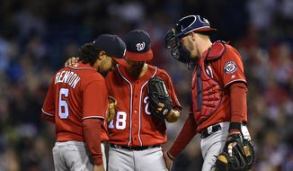 Washington Nationals' Anthony Rendon (6) and Matt Wieters, right, talk with starting pitcher Jeremy Guthrie, center, during the first inning of a baseball game against the Philadelphia Phillies, Saturday, April 8, 2017, in Philadelphia. (AP Photo/Derik Hamilton)