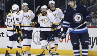 Nashville Predators' Matt Irwin (52), Colton Sissons (10), Ryan Ellis (4) and Austin Watson (51) celebrate Ellis' goal against the Winnipeg Jets during the second period of an NHL hockey game Saturday, April 8, 2017, in Winnipeg, Manitoba. (John Woods/The Canadian Press via AP)
