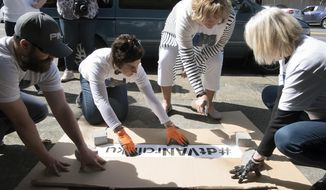 In this Friday, March 3, 2017 photo, volunteers for Vancouver's Downtown Association spray an invisible solution over a stencil spelling out #dtVANrainku in front of Vancouver's Downtown Association, in Vancouver, Wash. (Ariane Kunze /The Columbian via AP)
