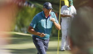 Matt Kuchar blows on his ball after hitting a hole in one on the 16th hole during the final round of the Masters golf tournament Sunday, April 9, 2017, in Augusta, Ga. (AP Photo/Matt Slocum)