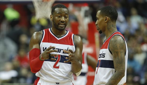 Washington Wizards guard John Wall (2) talks with teammate Brandon Jennings (7) during the second half of an NBA basketball game against the Miami Heat in Washington, Saturday, April 8, 2017. Miami won 106-103. (AP Photo/Pablo Martinez Monsivais)