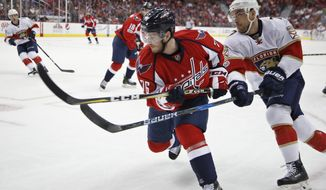 Washington Capitals right wing Garrett Mitchell (76) and Florida Panthers center Colton Sceviour (7) goes after the puck during the first period of an NHL hockey game in Washington, Sunday, April 9, 2017. The Panthers won 2-0. (AP Photo/Manuel Balce Ceneta)