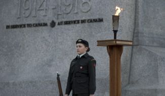 A sentry stands next to a torch of remembrance at the National War Memorial during a vigil to commemorate the 100th anniversary of the Battle of Vimy Ridge in Ottawa, Ontario, on Saturday, April 8, 2017. (Justin Tang/The Canadian Press via AP)