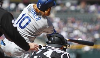 Los Angeles Dodgers' Justin Turner, right, connects for double to drive in two runs as Colorado Rockies catcher Tony Wolters looks on in the first inning of a baseball game Sunday, April 9, 2017, in Denver. (AP Photo/David Zalubowski)
