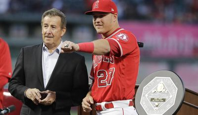 Los Angeles Angels' Mike Trout poses for photos with team owner Arte Moreno after he was received the American League MVP award, before the team's baseball game against the Seattle Mariners on Saturday, April 8, 2017, in Anaheim, Calif. (AP Photo/Jae C. Hong)