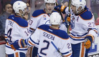 Edmonton Oilers' Jordan Eberle; Ryan Nugent-Hopkins; Andrej Sekera, of Slovakia; and Milan Lucic, from left, celebrate Eberle's goal against the Vancouver Canucks during the second period of an NHL hockey game Saturday, April 8, 2017, in Vancouver, British Columbia. (Darryl Dyck/The Canadian Press via AP)