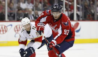 Washington Capitals center Evgeny Kuznetsov (92) skates with the puck while Florida Panthers left wing Jonathan Huberdeau (11) defends during the second period of an NHL hockey game in Washington, Sunday, April 9, 2017. (AP Photo/Manuel Balce Ceneta)
