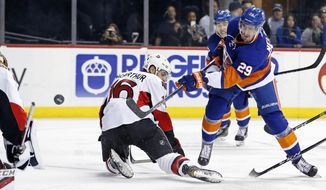 New York Islanders center Brock Nelson (29) takes a shot on net past Ottawa Senators left wing Clarke MacArthur (16) in the second period of an NHL hockey game, Sunday, April 9, 2017, in New York. (AP Photo/Adam Hunger)