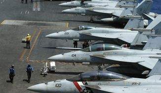 FILE - In this March 3, 2017 file photo, a row of F18 fighter jets on the deck of the USS Carl Vinson is prepared for patrols when the U.S. Navy took Philippine journalists to the mammoth aircraft carrier on routine patrol in the waters off the disputed South China Sea. The Pentagon says a Navy carrier strike group is moving toward the western Pacific Ocean to provide a physical presence near the Korean Peninsula. North Korea's recent ballistic missile tests and continued pursuit of a nuclear program have raised tensions in the region, where U.S. Navy ships are a common presence and serve in part as a show of force. The U.S. Pacific Command directed the carrier group, that includes the USS Carl Vinson, to sail north to the western Pacific after departing Singapore on Saturday, April 8, according to a Navy news release. (AP Photo/Bullit Marquez, File)