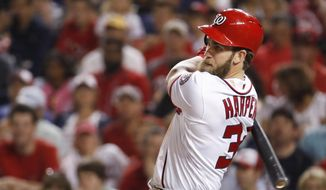 Washington Nationals Bryce Harper (34) watches the ball as he hits a single during the third inning of a baseball game against the St. Louis Cardinals in Washington, Monday, April 10, 2017. (AP Photo/Manuel Balce Ceneta)