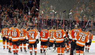 The Philadelphia Flyers raise their sticks in a show of appreciation to their fans at the close of the season and the NHL hockey game against the Carolina Hurricanes, Sunday, April 9, 2017, in Philadelphia. Carolina won 4-3. (AP Photo/Tom Mihalek)