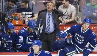 Vancouver Canucks coach Willie Desjardins, back, stands on the bench behind Michael Chaput, Brandon Sutter and Reid Boucher during the third period of an NHL hockey game against the Edmonton Oilers on Saturday, April 8, 2017, in Vancouver, British Columbia. (Darryl Dyck/The Canadian Press via AP)