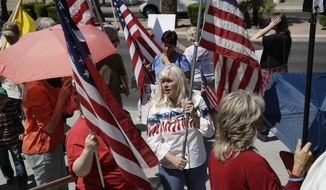 People rally in support of defendants on trial at a federal courthouse, Monday, April 10, 2017, in Las Vegas. Protesters gathered outside the courthouse in support of six defendants accused of wielding weapons against federal agents during a 2014 standoff involving cattleman and states' rights advocate Cliven Bundy. (AP Photo/John Locher)