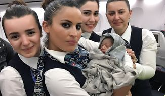 Turkish Airlines cabin crew are seen with baby Kadiju, who was born on a Guinea to Burkina Faso flight last week. (Photo courtesy of Turkish Airlines)