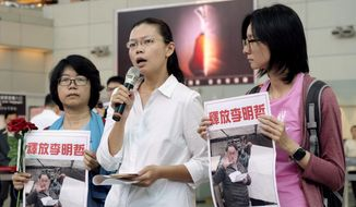 """Li Ching-yu, center, wife of Taiwanese pro-democracy activist Li Ming-che detained in China, gives a press conference after she was denied boarding the flight to Beijing at the airport counter at Taoyuan international airport in Taoyuan, Taiwan, Monday, April 10, 2017. Li Ching-yu told reporters that airline staff told her Beijing authorities had canceled her Chinese-issued travel permit when she tried to check in on Monday. Li had hoped to fly to China to demand information about her husband who has not been heard from since March 19. The sign in Chinese says """"Release/free Li Ming-che."""" (AP Photo/Johnson Lai)"""