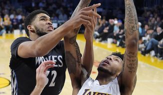 Minnesota Timberwolves center Karl-Anthony Towns, left, and Los Angeles Lakers forward Brandon Ingram reach for a rebound during the first half of an NBA basketball game, Sunday, April 9, 2017, in Los Angeles. (AP Photo/Mark J. Terrill)