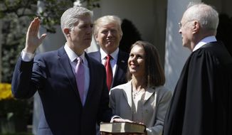 President Donald Trump watches as Supreme Court Justice Anthony Kennedy administers the judicial oath to Judge Neil Gorsuch during a re-enactment in the Rose Garden of the White House White House in Washington, Monday, April 10, 2017. Holding the bible is Gorsuch's wife Marie Louise Gorsuch. (AP Photo/Evan Vucci)