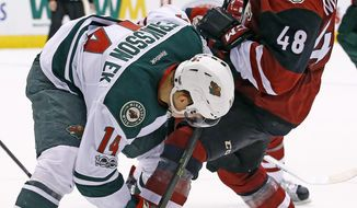 Minnesota Wild's Joel Eriksson Ek (14) sends Arizona Coyotes' Jordan Martinook (48) to the ice as they vie for the puck during the second period of an NHL hockey game Saturday, April 8, 2017, in Glendale, Ariz. (AP Photo/Ross D. Franklin)