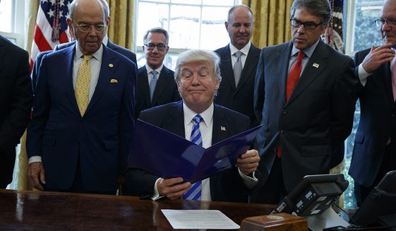 President Donald Trump, flanked by Commerce Secretary Wilbur Ross, left, and Energy Secretary Rick Perry, is seen in the Oval Office of the White House in Washington, Friday, March 24, 2107, file photo where he announced the approval of a permit to build the Keystone XL pipeline, clearing the way for the $8 billion project. (AP Photo/Evan Vucci) ** FILE **